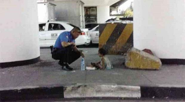 Traffic Enforcer I Reynaldo Romano was spotted feeding a street child in Commonwealth, March 12, Wednesday.